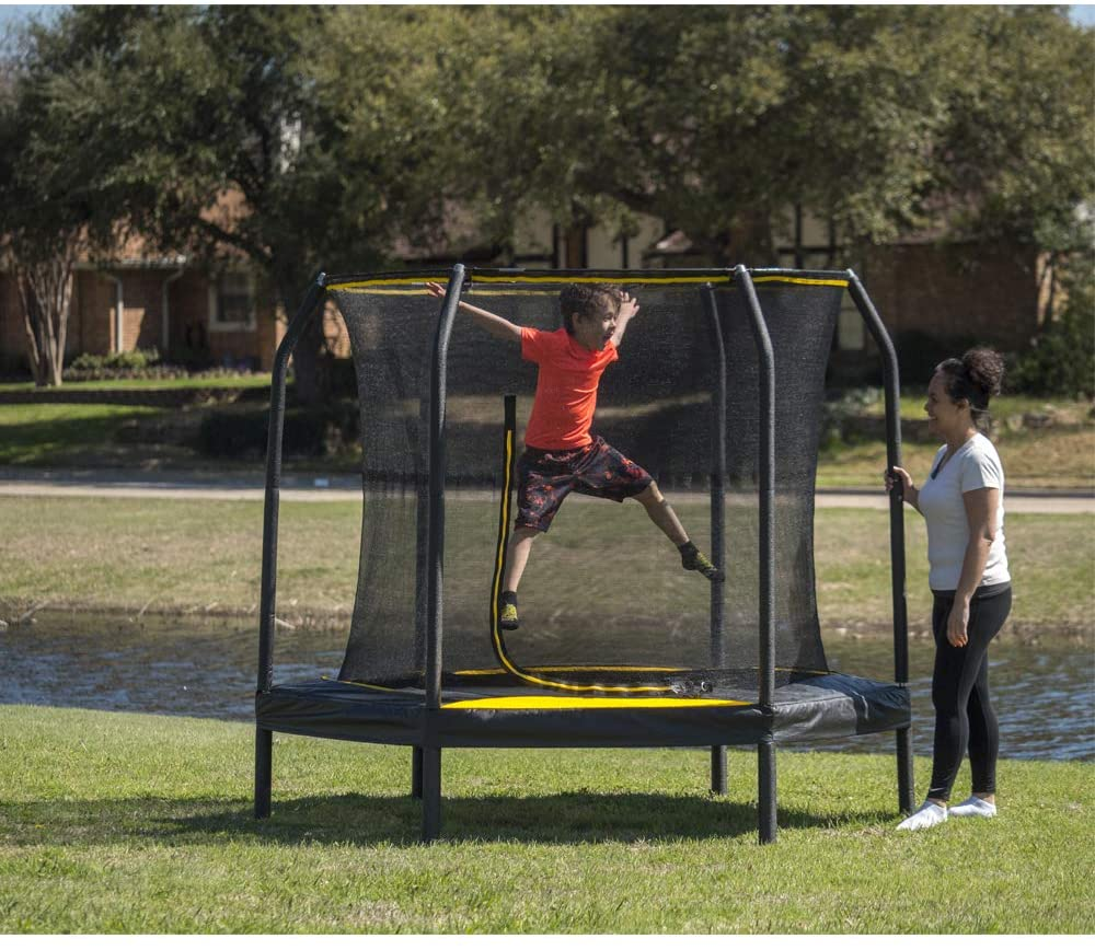 This is an image of JumpKing Black/Yellow 7.5-Foot Trampoline with Enclosure. The trampoline is placed outside on the wide sunny yard. A kid is happily jumping and looking at his mommy.