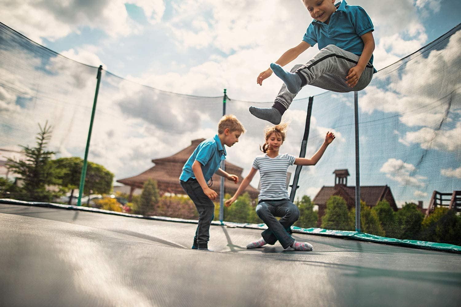 This is an image of 3 kids playing on 14FT Trampoline with Safety Enclosure Net