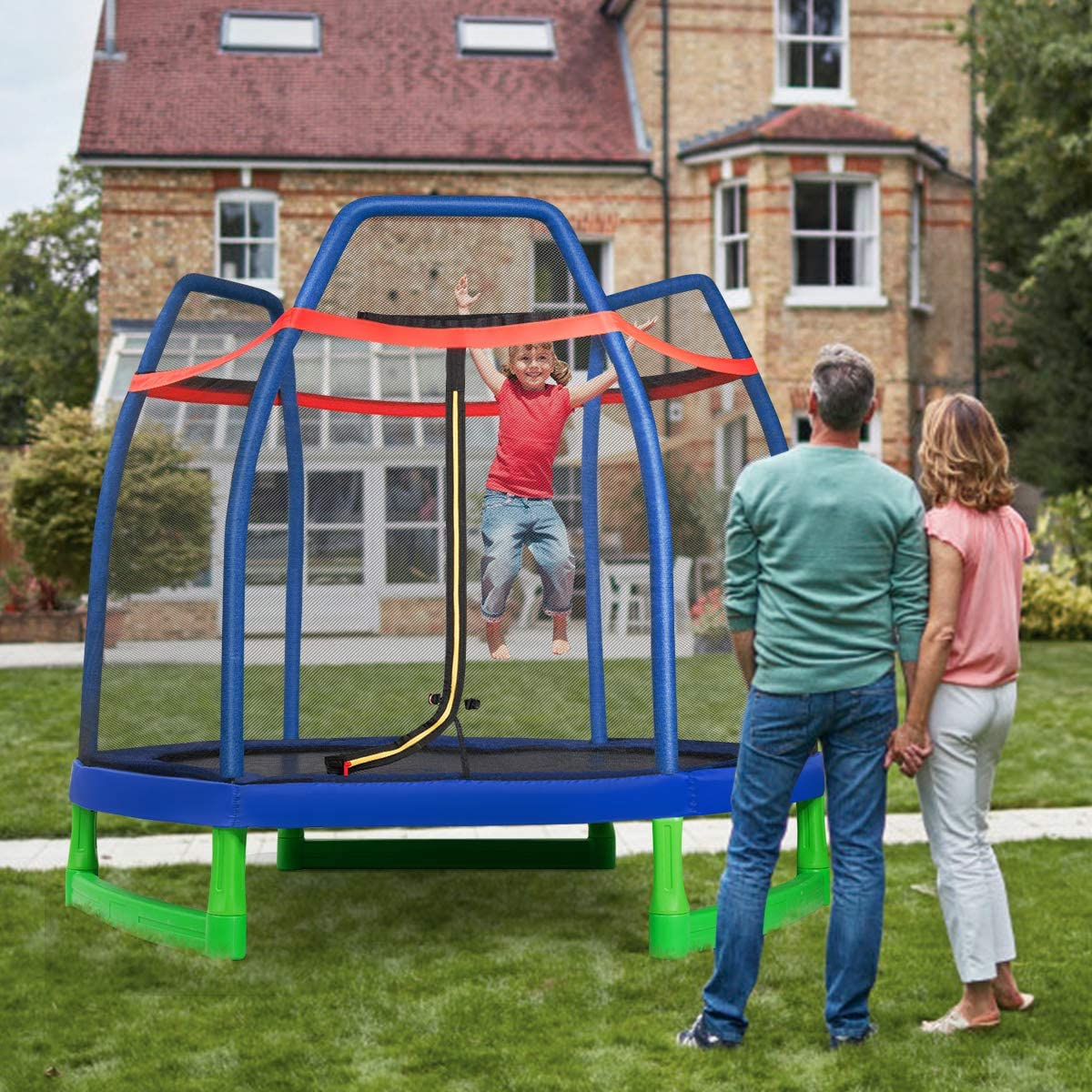 This is an image of GYMAX 7ft Kids Trampoline, Jumping Trampoline with Safety. Both parents are holding hands while observing the little boy jumping inside the trampoline.