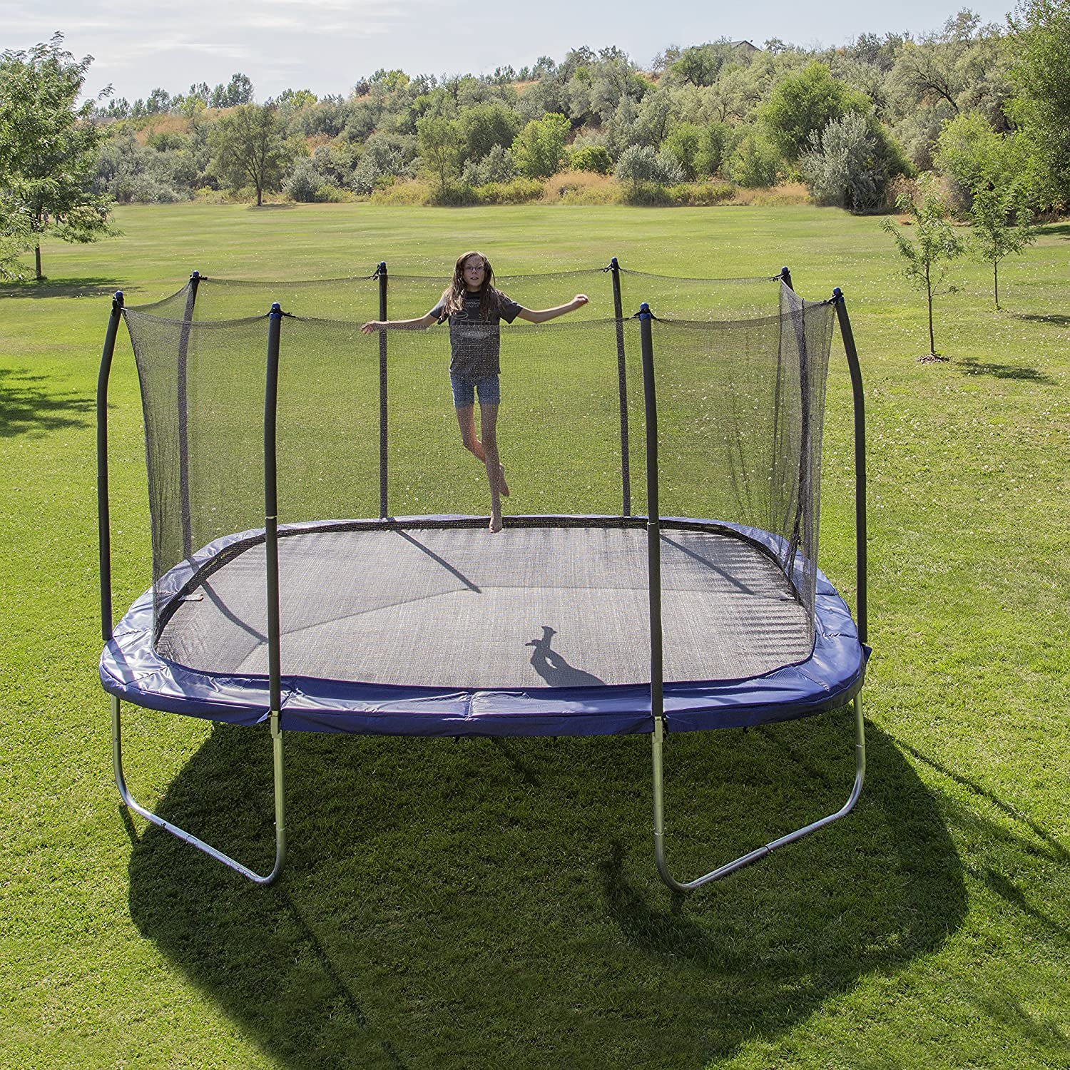 This is an image of Skywalker 14 ft Square Trampoline With Enclosure with a teenage girl jumping.