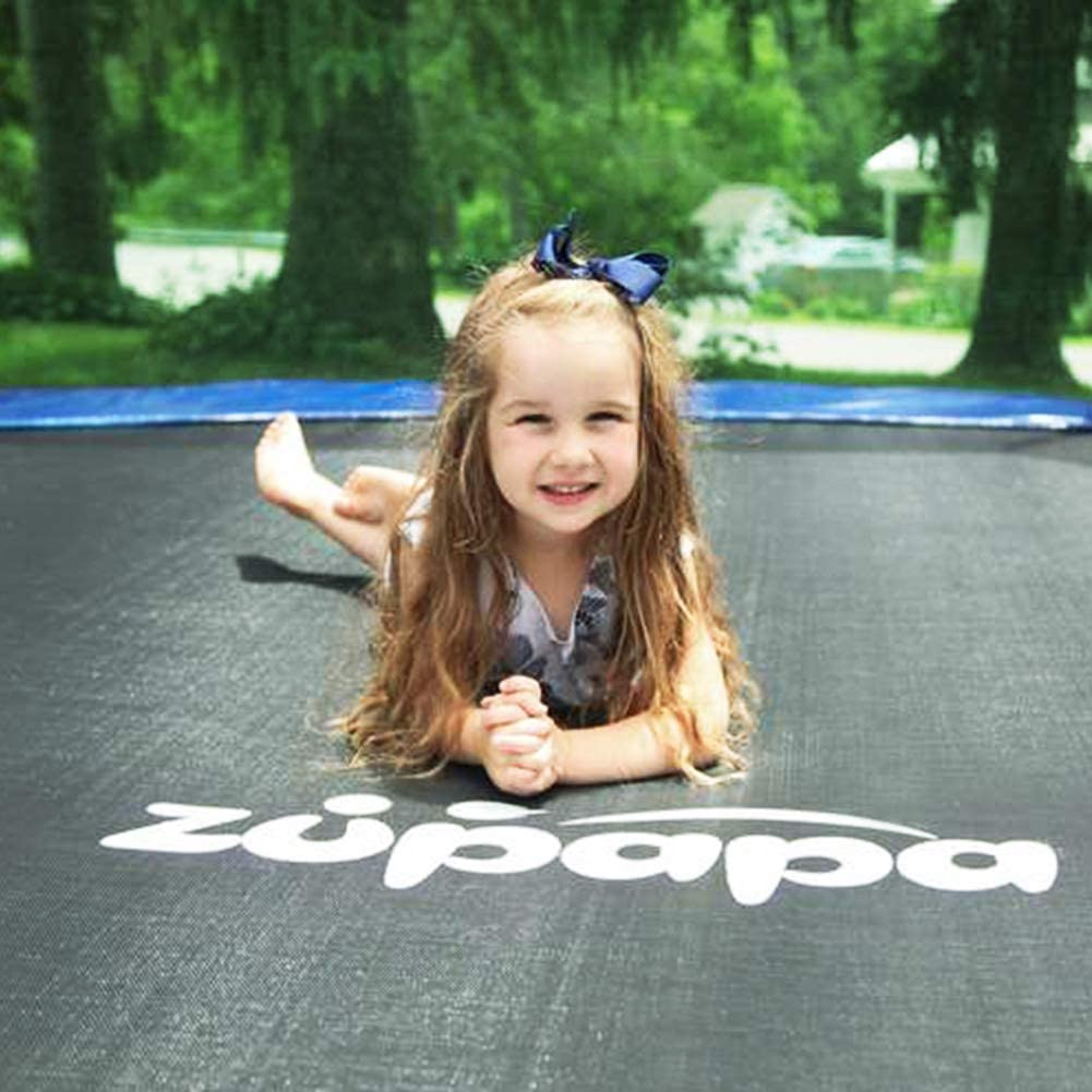This is an image of a baby girl smiling while lying on a safe trampoline with reasonable prices.